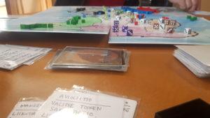 Kuvassa itsetehty pelilauta, nappuloita ja kortteja.